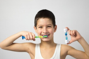 A child is brushing his teeth and smiling.
