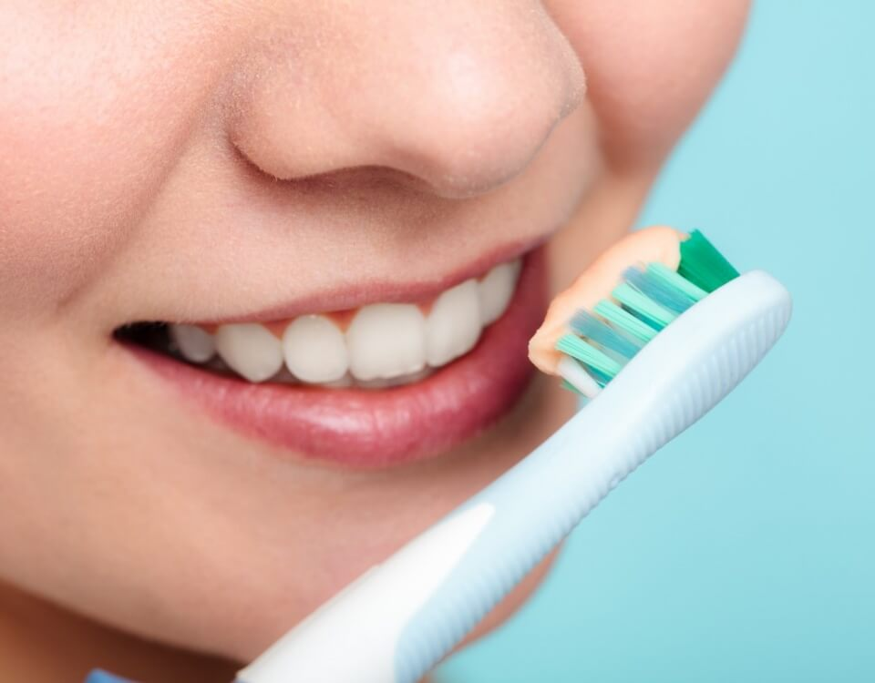 Woman cleaning her teeth using a toothbrush and toothpaste